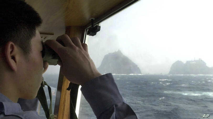 "FILE - A South Korean coast guard looks at Dokdo islets, known as ""Takeshima"" in Japanese, through a telescope on the patrol ship Sambong-ho on the East Sea, South Korea, April 28, 2005."