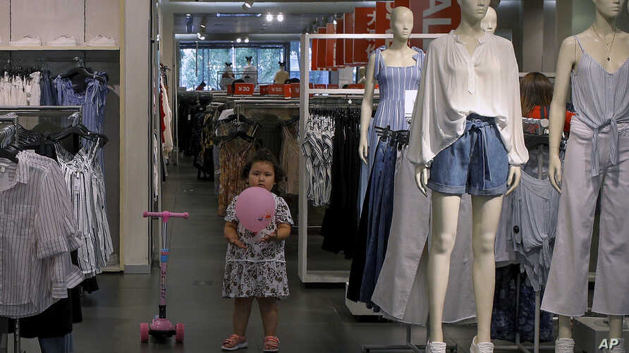 A child plays with a balloon at a clothing store having a promotion sale in Beijing, July 15, 2019. China's economic growth sank to its lowest level in at least 26 years.