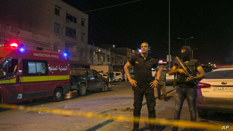 Tunisian police officers stand guard after police shot at a man wanted for terrorism in Al Intilaka, near Tunis, Tunisia Tuesday, July 2, 2019. Police shot at a man wanted for terrorism during a confrontation late Tuesday in Tunisia's capital and…
