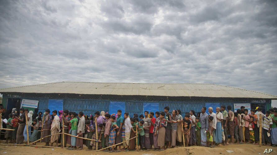 FILE - In this file photo dated Wednesday, Nov. 15, 2017, Rohingya Muslims, who crossed over from Myanmar into Bangladesh, wait in queues to receive aid at Kutupalong refugee camp in Ukhiya, Bangladesh.  The International Criminal Court prosecutor…