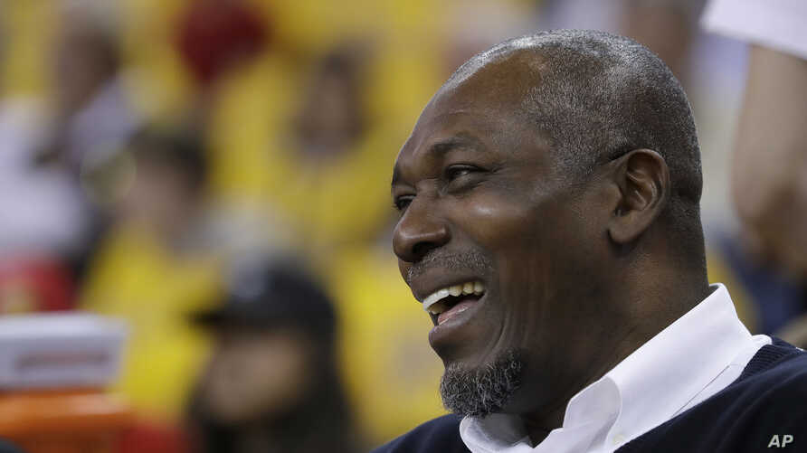 FILE - Hakeem Olajuwon, a former college athlete from Nigeria and a  Houston Rockets player, smiles before Game 6 of the NBA basketball Western Conference Finals in Oakland, Calif., May 26, 2018.
