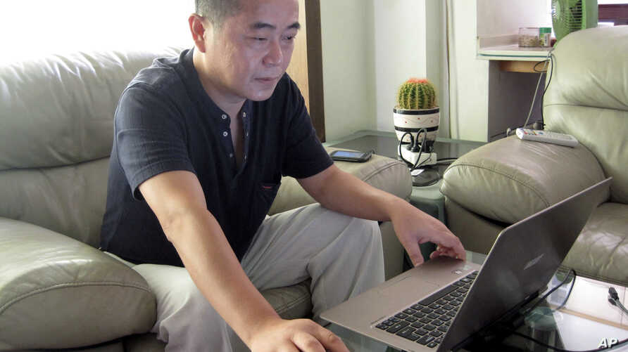 FILE - In this Sept. 18, 2012, file photo, veteran rights activist Huang Qi works on his laptop in his home in Chengdu in southwestern Sichuan province. Health worries afflicts longtime activist Huang, who operated a website that documented the…