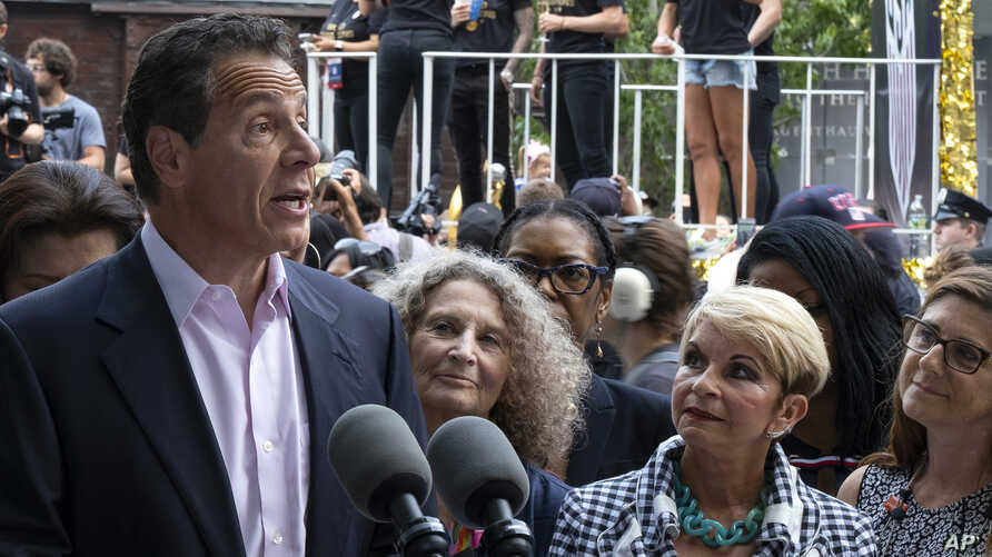 With members of the U.S. women's soccer team in the background before the start of a ticker tape parade in their honor, Gov. Andrew Cuomo speaks before signing a bill into law Wednesday, July 10, 2019, in New York. The bill will expand a law banning…