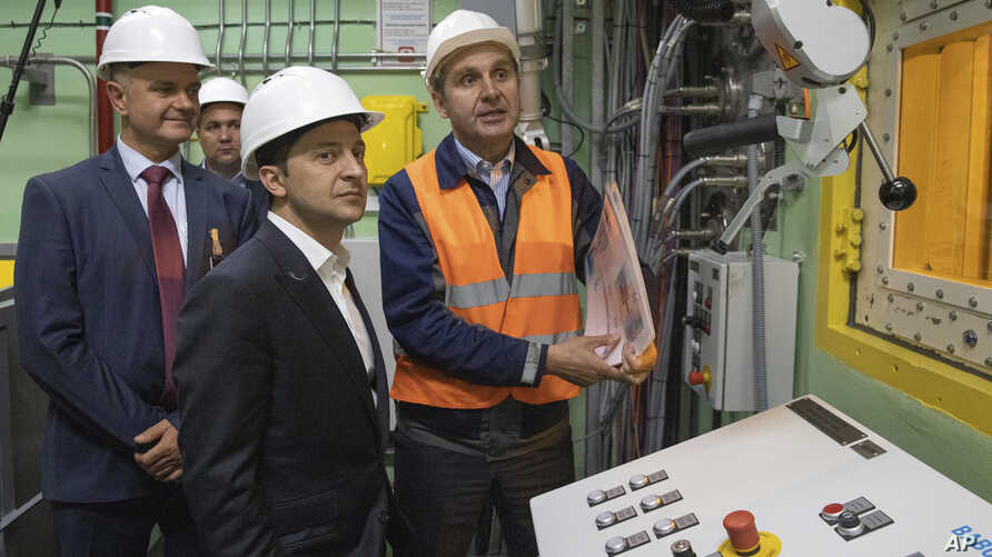 """Ukrainian President Volodymyr Zelenskiy, foreground, visits the """"new safe confinement"""" shelter that spans the remains of the Chernobyl nuclear power plant's Reactor No. 4, in Chernobyl, Ukraine,  July 10, 2019."""
