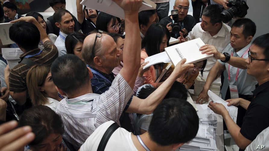 Reporters scramble to get copies of the China's national defense white paper before a press conference at the State Council Information Office in Beijing, July 24, 2019.