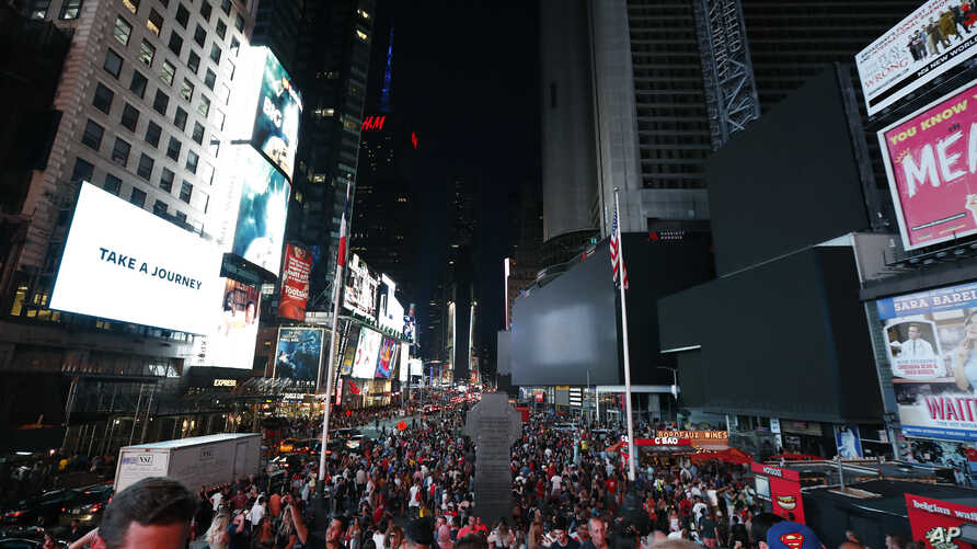 Screens in Times Square are black during a power outage, July 13, 2019, in New York. The outage knocked out Times Square's electronic screens, darkened marquees in the theater district and left businesses dark, elevators stuck and subway cars stalled.