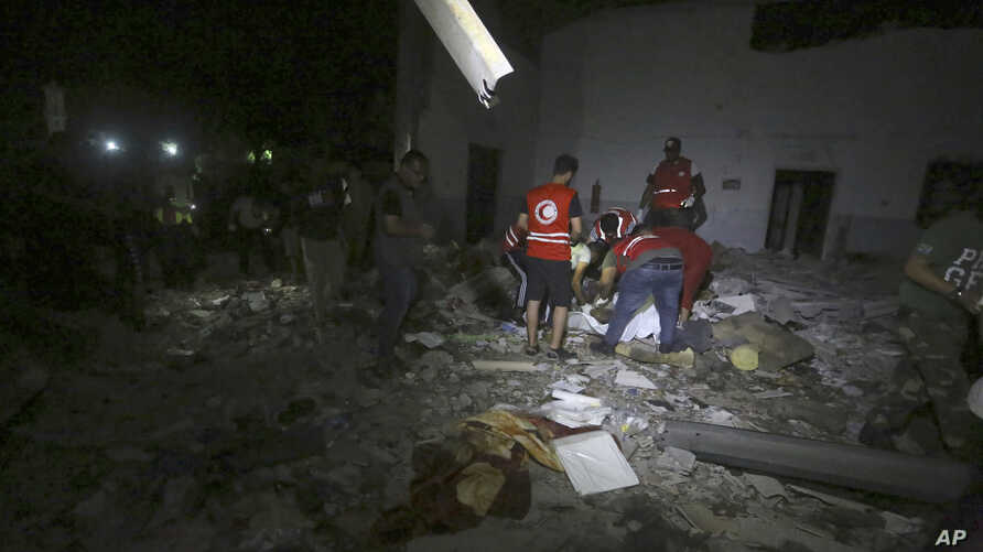 Libyan Red Crescent workers recover migrants bodies after an airstrike at a detention center in Tajoura, east of Tripoli Wednesday, July 3, 2019. An airstrike hit the detention center for migrants early Wednesday in the Libyan capital. (AP Photo…