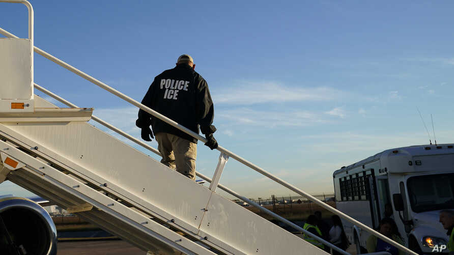 FILE - In this Nov. 16, 2018, file photo, an officer watches as immigrants who entered the United States illegally are deported on a flight to El Salvador by U.S. Immigration and Customs Enforcement in Houston. Civil rights activists complained…