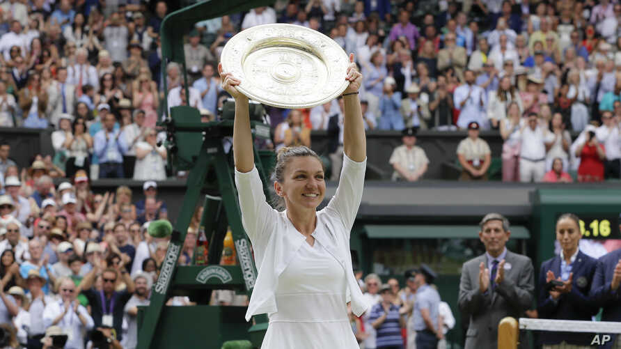 Romania's Simona Halep holds the trophy after defeating United States' Serena Williams during the women's singles final match on day twelve of the Wimbledon Tennis Championships in London, Saturday, July 13, 2019. (AP Photo/Kirsty Wigglesworth)