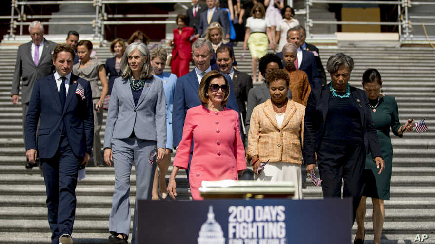 In this July 25, 2019, photo, House Speaker Nancy Pelosi of Calif., and House Democrats arrive for a news conference on the first 200 days of the 116th Congress at the House East Front steps of the Capitol in Washington. Nearly half the House…