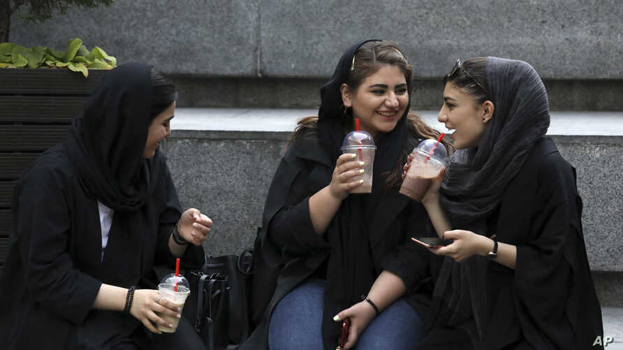 In this Tuesday, July 2, 2019 photo, youngsters spend an afternoon while siting on steps outside a shopping mall in northern Tehran, Iran.  A few daring women in Iran's capital have been taking off their mandatory headscarves, or hijabs, in public,…