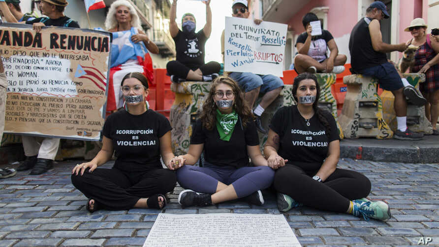 Three women sit with their mouths taped shut outside the government mansion La Fortaleza, where a small group of protesters gathered in San Juan Puerto Rico, Friday, Aug. 9, 2019.  The protests that led to the resignation of Gov. Ricardo Rossello on…