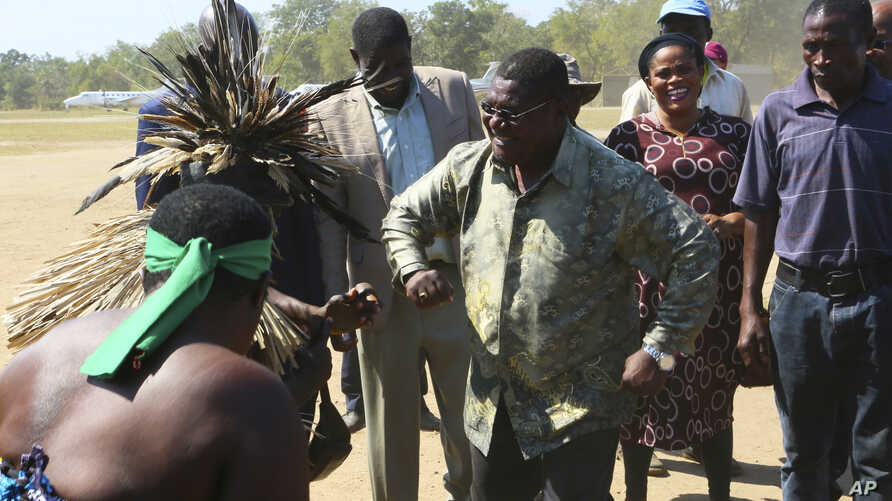 Renamo leader Ossufo Momade, center, performs a dance with locals upon his arrival for a peace accord signing ceremony at Gorongosa National Park, about 170 kilometres from Beira, Mozambique, Thursday, Aug, 1, 2019. Momade is set to sign a peace…