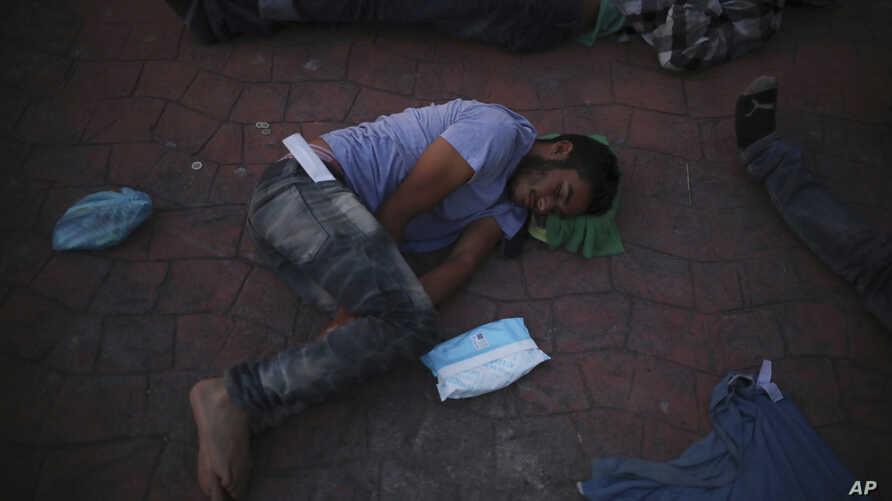 A migrant who returned from the U.S. the previous day sleeps outside a Mexican immigration office in Matamoros, Mexico, Sunday, Aug. 4, 2019, on the border with the U.S. Many immigrants at the border are either in line for an initial attempt to seek…