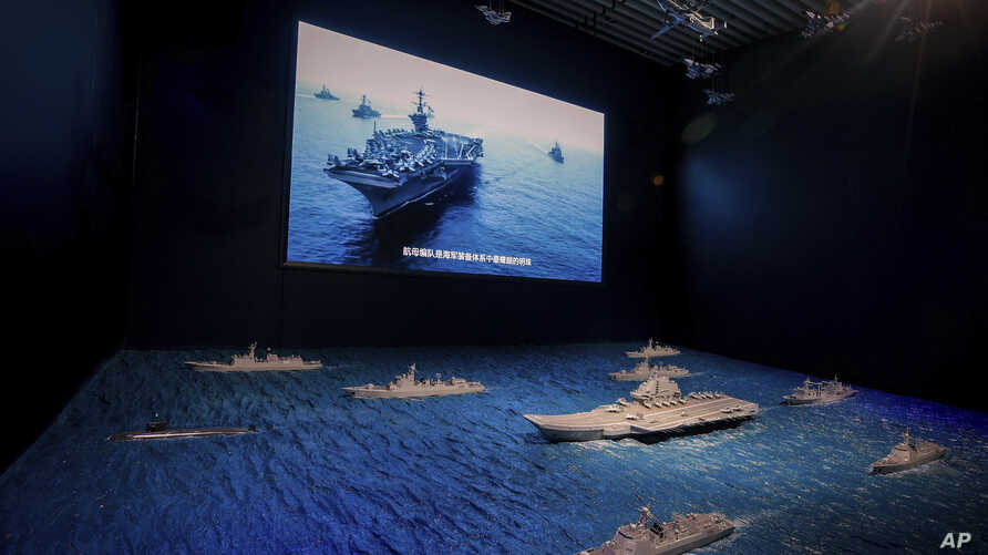 A TV screen showing the U.S. Navy fleet sail in formation near the models of Liaoning aircraft carrier with navy frigates and submarines on display at the military museum in Beijing, Thursday, Aug. 1, 2019. U.S. Secretary of State Mike Pompeo said…