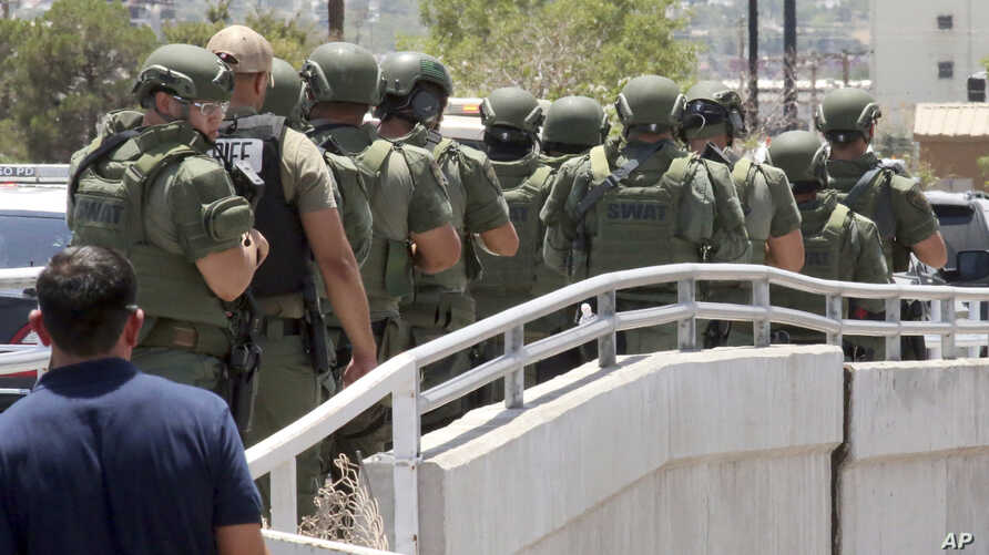 Law enforcement officers make their way along a walkway to the scene of a shooting at a shopping mall in El Paso, Texas, on Saturday, Aug. 3, 2019.   Several people were killed in the shooting Saturday in a busy shopping area in the Texas border…