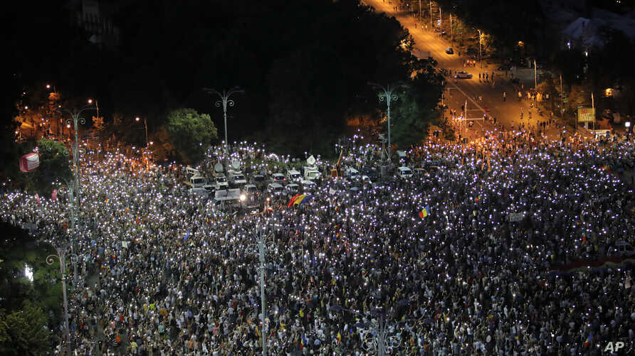 People flash the light of their mobile phones during an anti-government protest in Victoria Square, outside the government headquarters in Bucharest, Romania, Saturday, Aug. 10, 2019. Thousands joined a protest, one year after a similar rally turned…