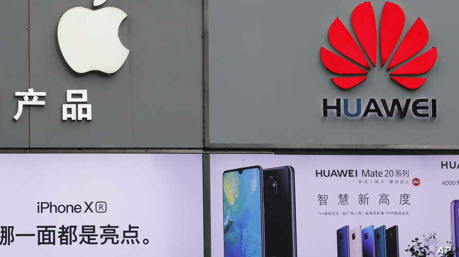 FILE - In this Thursday, March 7, 2019, file photo, logos of Apple and Huawei are displayed outside a mobile phone retail shop in Shenzhen, China's Guangdong province. Few U.S. companies are more vulnerable to a trade war with China than Apple. The…