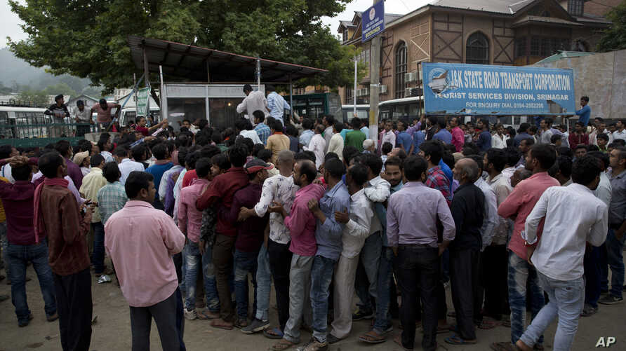 Indian migrant workers wait outside the government transport yard waiting to buy bus tickets to leave the region, during curfew in Srinagar, Indian controlled Kashmir, Aug. 7, 2019.