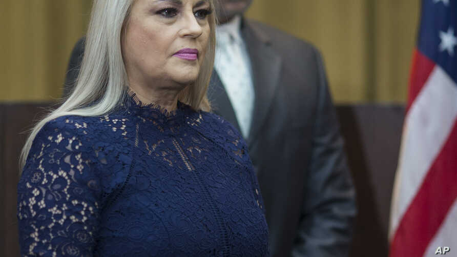 Justice Secretary Wanda Vazquez is accompanied by her husband Judge Jorge Diaz during her swearing in ceremony as Puerto Rico's new governor, in San Juan, Puerto Rico, Wednesday, Aug. 7, 2019. Vazquez took the oath of office early Wednesday evening…