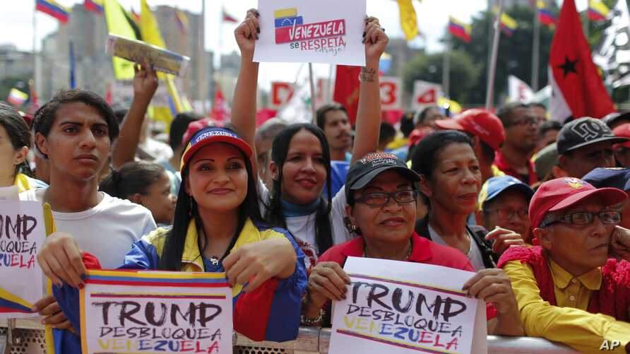 """Government supporters hold signs with a message that reads in Spanish: """"Trump unblock Venezuela"""" during a protest against U.S. sanctions, in Caracas, Venezuela, Wednesday, Aug. 7, 2019. Sweeping new U.S. sanctions freeze all of the Nicolas Maduro…"""