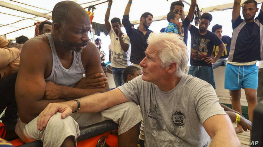 Actor Richard Gere, right, talks with migrants aboard the Open Arms Spanish humanitarian boat as it cruises in the Mediterranean Sea, Friday, Aug. 9, 2019. Open Arms has been carrying 121 migrants for a week in the central Mediterranean awaiting a…