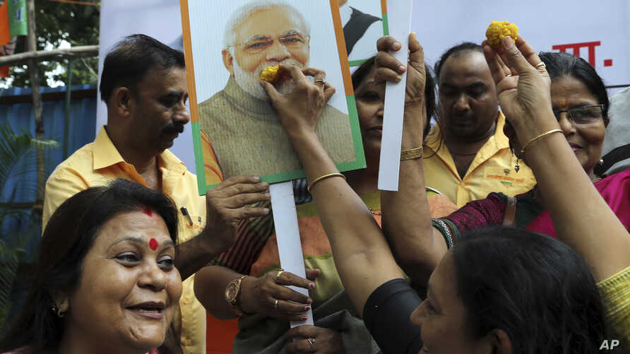 A supporter of India's ruling Bhartiya Janata Party (BJP) feeds sweets to a portrait of Prime Minister Narendra Modi as she celebrates with others the revocation of Kashmir's special constitutional status, in Mumbai, India, Tuesday, Aug. 6, 2019…