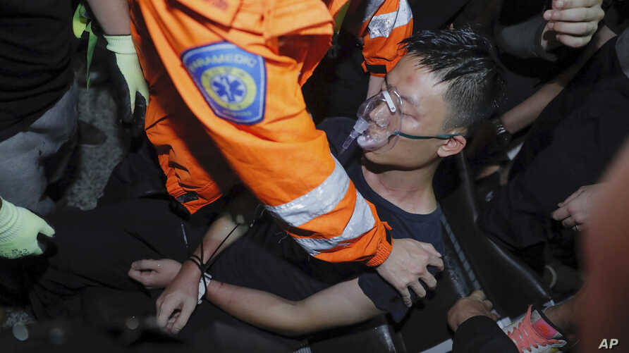 A medical staffer helps a detained man, who protesters claimed was a police officer from mainland China, during a demonstration at the Airport in Hong Kong,  Aug. 13, 2019.