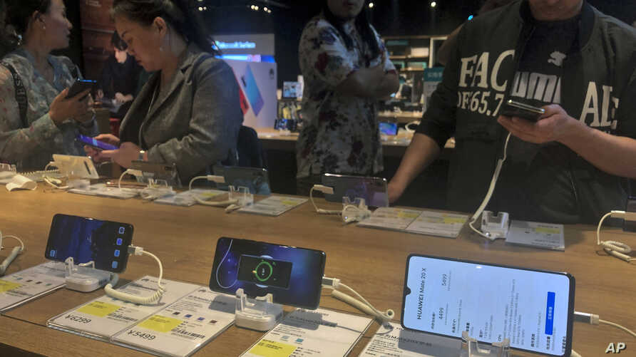 People try out Huawei smartphone models on display at an electronic store in Beijing, Monday, May 20, 2019. Google assured users of Huawei smartphones on Monday the American company's basic services will work on them following U.S. government cubs…