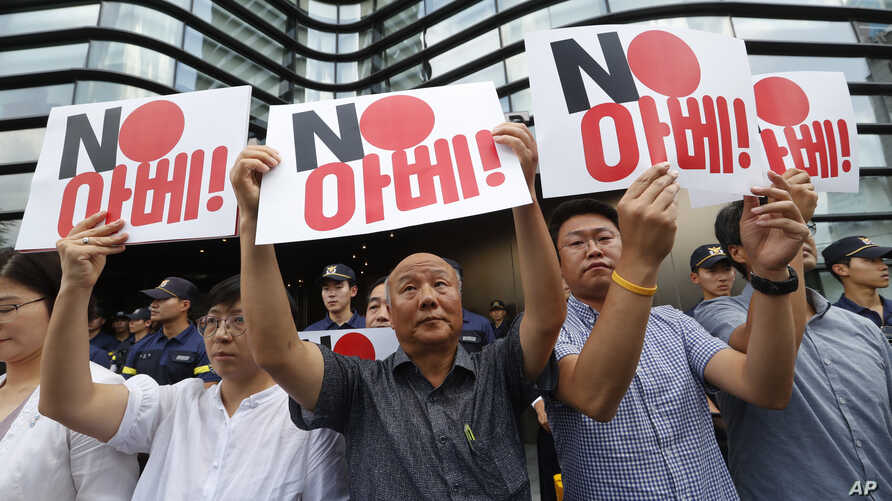 """South Korean protesters hold up cards during a rally against Japan in front of a building that houses the Japanese embassy in Seoul, South Korea, Aug. 2, 2019.  The signs read """" Japanese Prime Minister Shinzo Abe."""""""