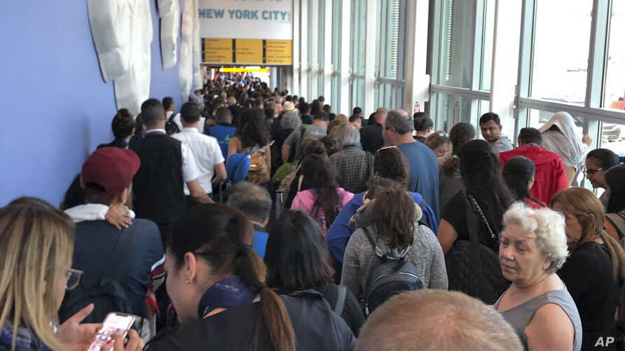 In this photo provided by Twitter user Ninis Samuel, travelers stand in long lines to clear Customs at John F. Kennedy International Airport, Friday, Aug. 16, 2019, in New York, due to a temporary computer outage that affected U.S. Customs and…