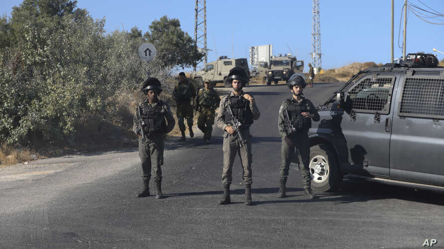 Israeli troops secure the area where a body of a soldier with stab wounds was found near Gush Etzion settlement in the West Bank, Aug, 8, 2019.