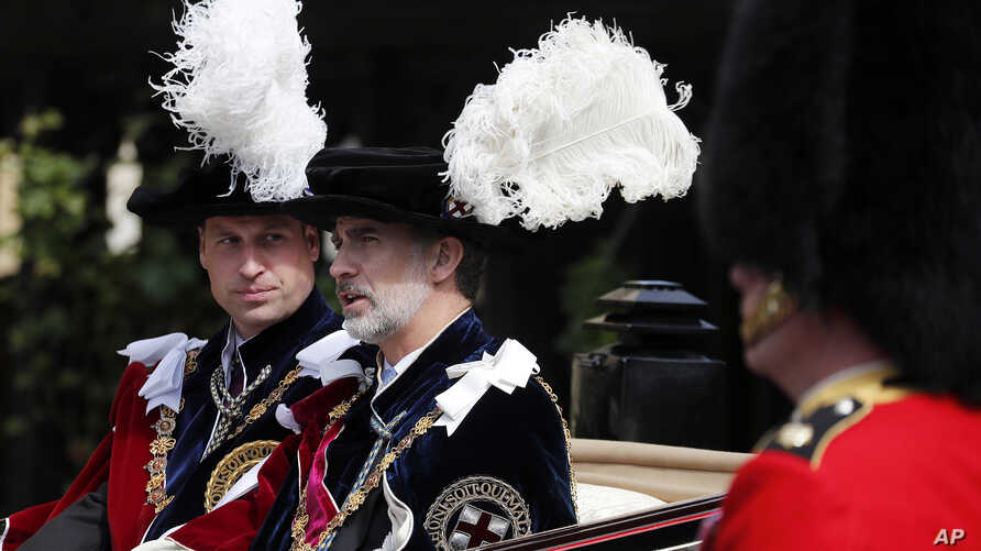 Britain's Prince William, left, and Spain's King Felipe sit in a carriage after the Order of The Garter Service at Windsor Castle in Windsor, June 17, 2019.