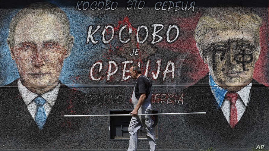 """A man passes by graffiti depicting the Russian President Vladimir Putin, left, and US President Donald Trump in Belgrade, Serbia, Friday, Aug. 9, 2019. The Cyrillic letters on graffiti read """"Kosovo is Serbia"""". A former Serbian province, Kosovo…"""