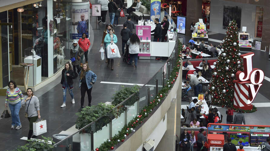 FILE- In this Dec. 22, 2017, file photo people shop at the Pentagon City Mall in Arlington, Va.