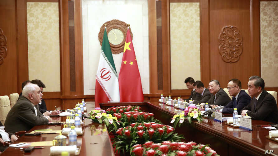 Iranian Foreign Minister Mohammad Javad Zarif, left, speaks with Chinese Foreign Minister Wang Yi during their meeting at the Diaoyutai State Guesthouse in Beijing, Aug. 26, 2019. (How Hwee Young/Pool Photo via AP)