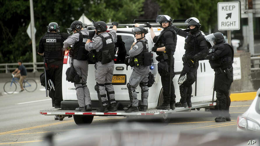 """Police officers ride on the side of a van as right-wing demonstrators and counter-protesters gather in Portland, Ore., for an """"End Domestic Terrorism"""" rally on Saturday, Aug. 17, 2019.  Police seized metal poles, bear spray and other weapons as…"""