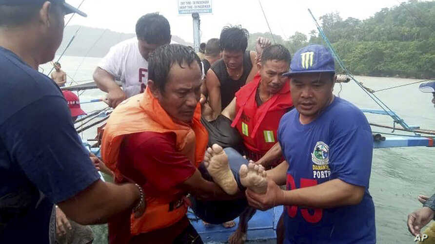 Coast guard rescuers and volunteers carry a victim after being retrieved from the waters off Guimaras, Aug. 4, 2019 in Iloilo province in central Philippines.