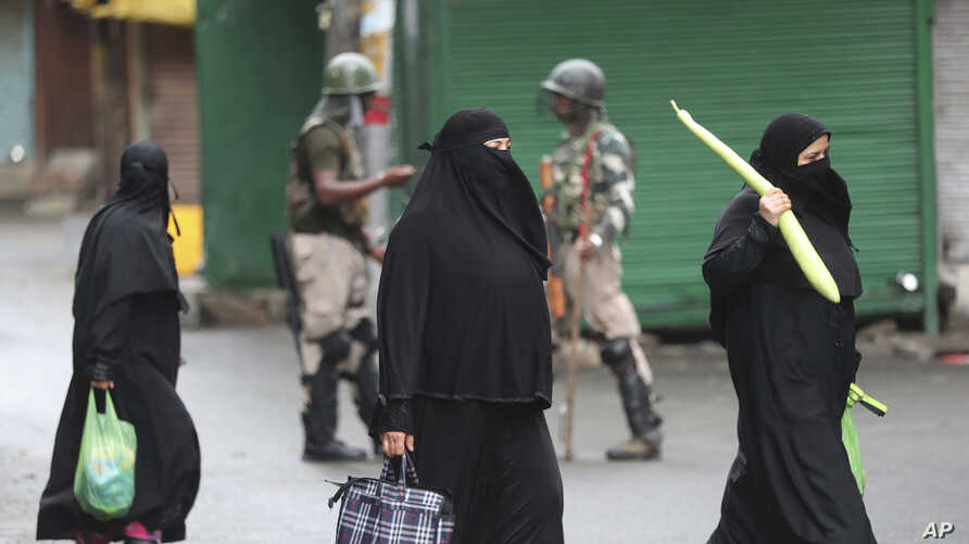 Kashmiri women carry bags filled with essentials past Indian paramilitary soldiers closing off a street in Srinagar, Indian-controlled Kashmir, Aug. 10, 2019.