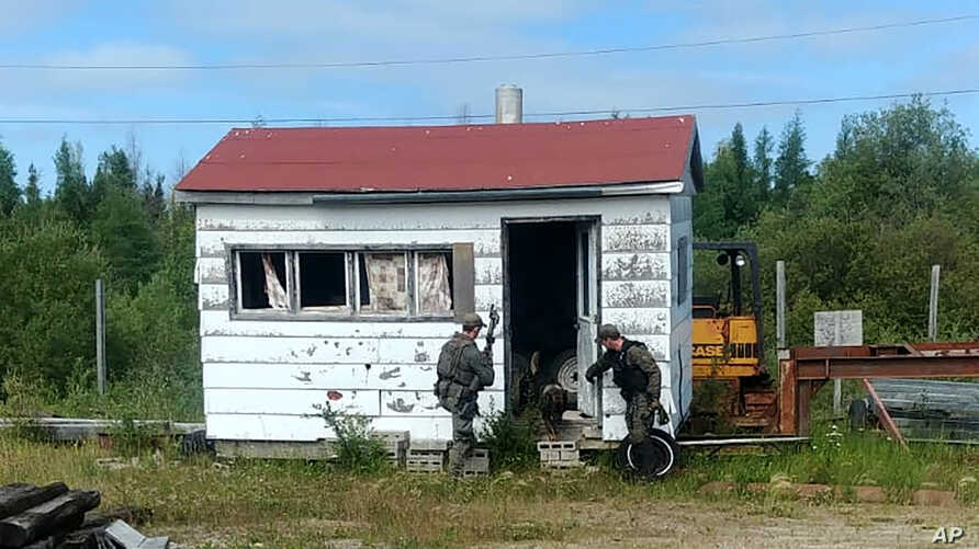 In this recent photo provided by the Royal Canadian Mounted Police, RCMP officers canvas homes and buildings in the Gillam, Manitoba area, as they continue to search for two teenagers being sought in the killings of three people in northern British…