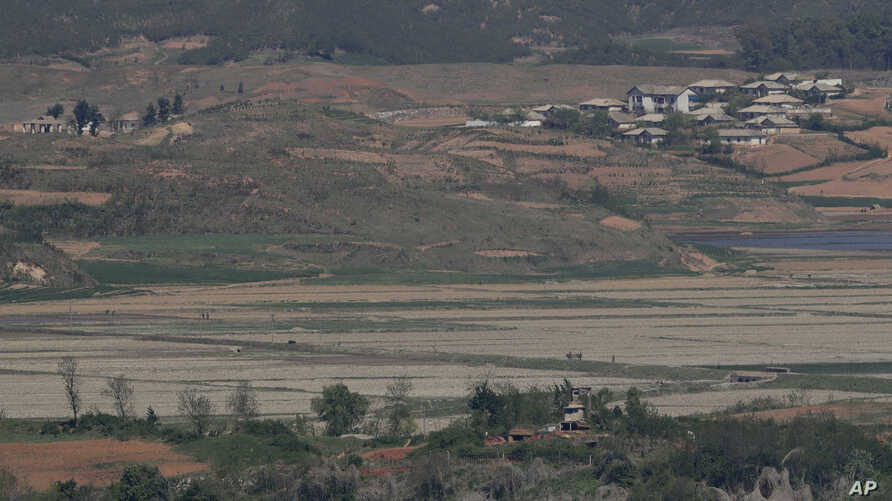 North Korea's Kaepoong town is seen behind a North Korean military guard post, bottom, from the unification observatory in Paju, South Korea, May 6, 2019.  North Korea says it is suffering its worst drought in decades amid concern of a food crisis.