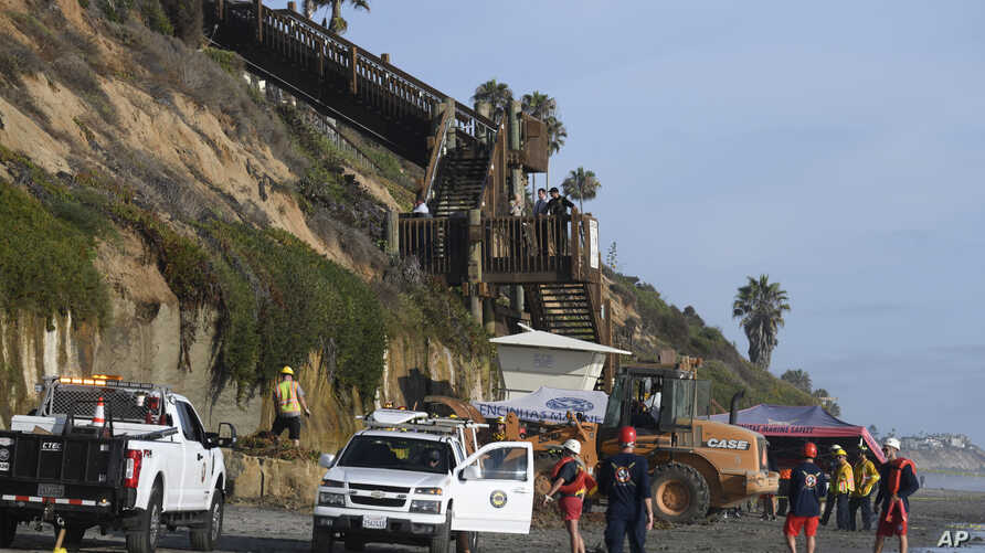 Lifeguards and search and rescue personnel work at the site of a cliff collapse, Aug. 2, 2019, in Encinitas, Calif. At least three people were killed when an oceanfront bluff collapsed at Grandview Beach.