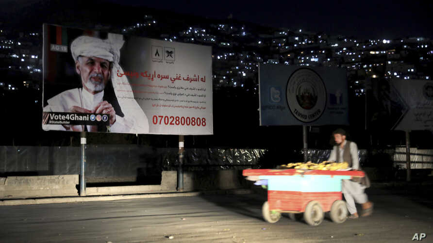 In this Sept. 9, 2019, photo, an Afghan street vendor pulls his hand cart in front of an election poster of Afghan President Ashraf Ghani, who seeks a second term, in Kabul, Afghanistan. President Donald Trump's sudden halt to U.S.-Taliban talks…