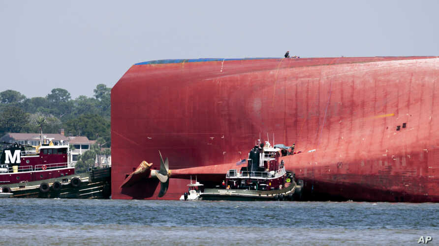 Rescuers work near the stern of the vessel Golden Ray as it lays on its side near the Moran tug boat Dorothy Moran, Monday, Sept. 9, 2019, in Jekyll Island, Ga. Coast Guard rescuers have made contact with four South Korean crew members trapped…