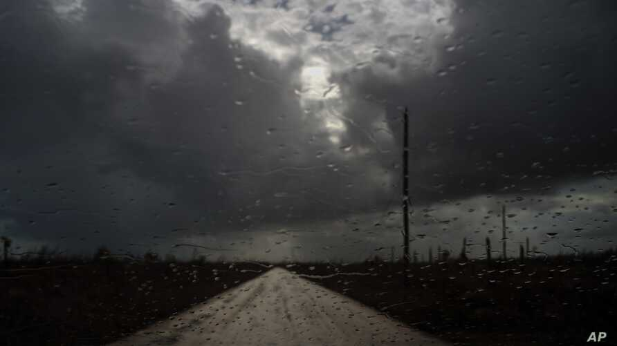 Rain prior to the arrival of the tropical depression falls on the windshield of a car in the aftermath of Hurricane Dorian at the route of Mclean's Town, Grand Bahama, Bahamas, Friday Sept. 13, 2019. (AP Photo/Ramon Espinosa)