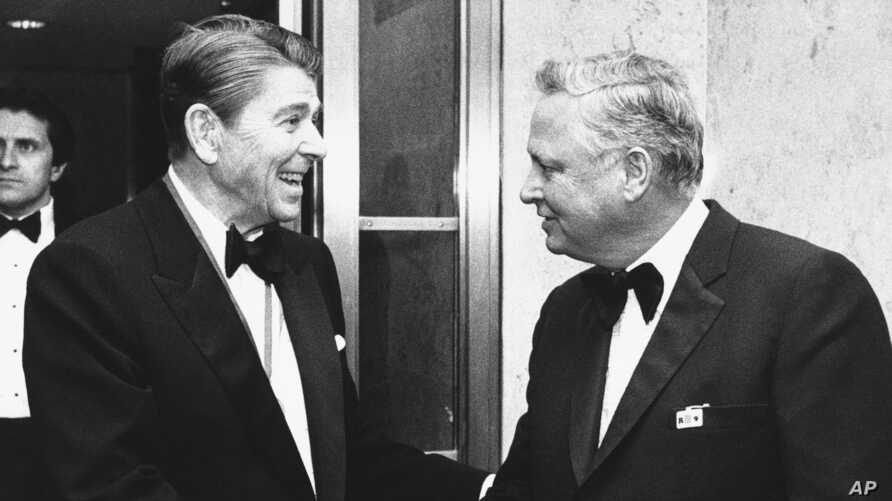 FILE - In this Jan. 26, 1985 file photo, President Ronald Reagan, left, shakes hands with Barron Hilton upon his arrival at the Capitol Hill in Washington to attend the annual Alfalfa Club meeting. Hilton, a hotel magnate who expanded his father's…