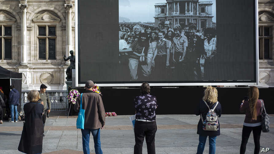 People watch former President Jacques Chirac on a giant screen set up at the Paris town hall Paris, Friday, Sept. 27, 2019. Mourners are signing memory books, flags are lowered and French politicians from across the spectrum are paying tributes to…