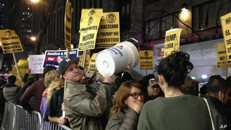 """Demonstrators march to protest Donald Trump's views on immigration hours before he hosts """"Saturday Night Live,"""" Saturday, Nov. 7, 2015, in New York. Dozens of protesters held signs and chanted Saturday evening as they marched from Trump Tower to NBC…"""