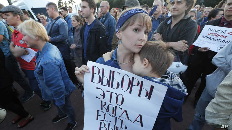 A woman holds a poster that reads: 'Elections are when you can choose', as people gathered for a protest in St.Petersburg, Russia, Thursday, Sept. 5, 2019. About 400 people gathered for a meeting against the violations and no-alternative governor…