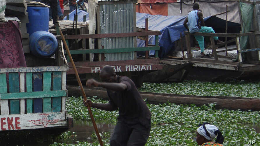 A man paddles a dugout canoe past whaleboats being loaded with cargo and passengers at Baramoto Port in Kinshasa, Congo Monday, Sept. 6, 2010. In a country of dense rain forests with few paved roads, boarding an overcrowded boat on a treacherous…